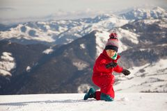 Portrait of happy little girl playing on the top of mount with ice and snow royalty free stock photo