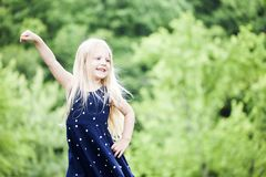Portrait of happy little girl posing in blue dotted dress royalty free stock photos