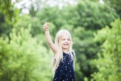 Portrait of happy little girl raising arm stock photography