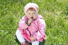 Portrait of happy little girl resting on green grass in the park Royalty Free Stock Photography