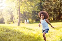 Portrait of happy little girl running on grass land stock photo