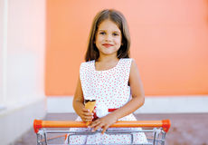 Portrait happy little girl in shopping cart with tasty ice cream Royalty Free Stock Images
