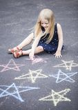 Portrait of happy little girl sitting on asphalt and drawing royalty free stock images