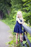 Portrait of happy little girl standing on railing in park stock images