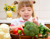 Portrait of a happy little girl with vegetables. In the kitchen Stock Photos