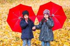 Happy little girls laughing with umbrellas in the rain stock photo