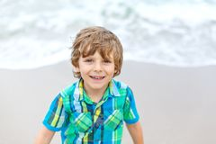 Portrait of happy little kid boy on the beach of ocean. Funny cute child making vacations and enjoying summer. Healthy stock photo