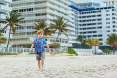 Portrait of happy little kid boy on the beach of ocean. Funny cute child making vacations and enjoying summer. Healthy stock photography
