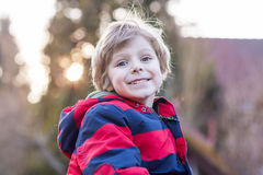 Portrait of happy little kid boy in red jacket, outdoors Royalty Free Stock Photography