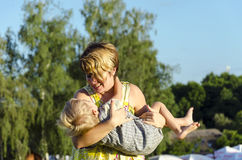 Portrait of happy little mom kissing and shake son outdoors on green summer garden. Royalty Free Stock Images