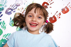 Painting. Portrait of a happy little school girl playing with colors royalty free stock image