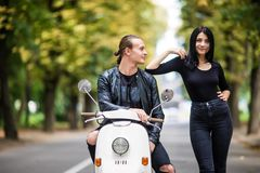 Portrait of happy young love couple on scooter enjoying themselves in a park at summer time Stock Photos