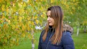 Portrait of happy lovely and beautiful young woman in forest in fall colors. Girl walking in the autumn city Park. 4k stock video footage