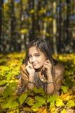 Portrait of happy lovely teenage girl holding lying on  autumn f Stock Photos