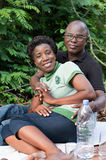Portrait of happy loving couple sitting in the forest. Stock Photography