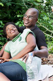 Portrait of happy loving couple sitting in the forest. Stock Image