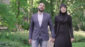 Portrait of happy loving Middle Eastern couple strolling in sunny summer park. Middle shot of smiling bearded man and