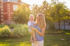 Portrait of happy loving mother and her baby outdoors. Stock Photos
