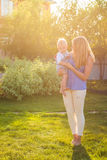 Portrait of happy loving mother and her baby outdoors. Royalty Free Stock Images