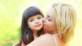 Portrait happy loving mother kissing child outdoors in summer stock photo
