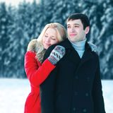 Portrait happy loving young couple hugging in winter day over snowy trees forest Stock Images