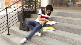 Portrait of a happy male asian student sitting on stairs and reading book stock footage