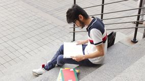 Portrait of a happy male asian student sitting on stairs and reading book stock video footage