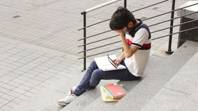 Portrait of a happy male asian student sitting on stairs and reading book stock video