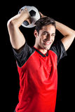 Portrait of happy male athlete throwing football Stock Images