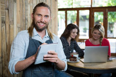 Portrait of happy male barista writing orders in coffee shop. Portrait of happy male barista writing orders with female customers in background at coffee shop Royalty Free Stock Photo