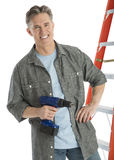 Portrait Of Happy Male Carpenter Holding Drill. While standing against white background Stock Photography