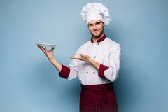 Portrait of a happy male chef cook standing with plate isolated on light blue background. royalty free stock photos