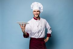 Portrait of a happy male chef cook standing with plate isolated on light blue background. stock images