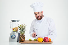 Portrait of a happy male chef cutting fruit Royalty Free Stock Images