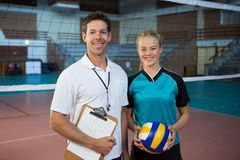 Happy male coach and volleyball player standing in the court. Portrait of happy male coach and volleyball player standing in the court Royalty Free Stock Images