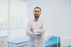 Portrait of a happy male doctor standing with arms crossed at medical office.  Stock Image