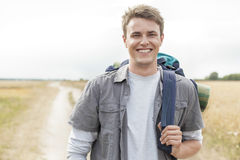 Portrait of happy male hiker with backpack standing on field Stock Photography