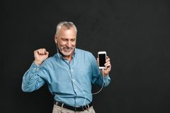 Portrait of happy male pensioner 60s with gray hair dancing whil. E listening to music via white earphones using mobile phone isolated over black background Stock Photo