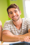 Portrait of happy male student in library. Portrait of happy male student doing homework in the library Stock Photos