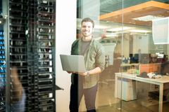 Network technician in data center. Portrait of happy male technician with laptop in large data center royalty free stock photography