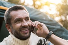 Carefree young man talking on mobile phone in forest Royalty Free Stock Photo