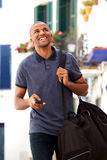 Happy male traveler walking in city. Portrait of happy male traveler walking in city with mobile phone and bag Stock Photos
