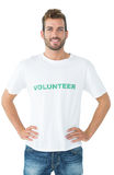Portrait of a happy male volunteer standing with hands on hips stock photo
