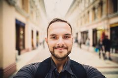 Portrait of a happy man with beard taking selfie. Hipster tourist smiles into the camera. Blurred background.