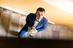 Portrait of happy man in blue suit on stairs smiling holding bouquet. View from the top Royalty Free Stock Images
