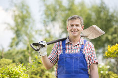 Portrait of happy man carrying spade on shoulder in plant nursery stock image