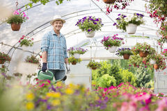 Portrait of happy man carrying watering can in greenhouse Royalty Free Stock Photo