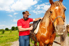 Portrait of happy man in cowboy hat saddling horse. Portrait of happy young man in cowboy hat saddling beautiful horse at the farm Royalty Free Stock Image