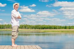 Portrait of a happy man in full length on a wooden pier on the b. Ackground of a beautiful lake stock photo