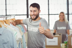Portrait of happy man gesturing thumbs up while selecting clothes Royalty Free Stock Photography